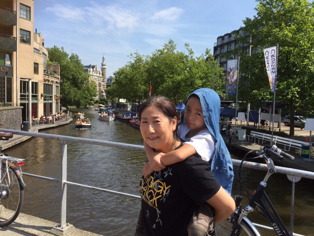 Jin Wen, a bit ill, carried by his aunt through the Amsterdam channels