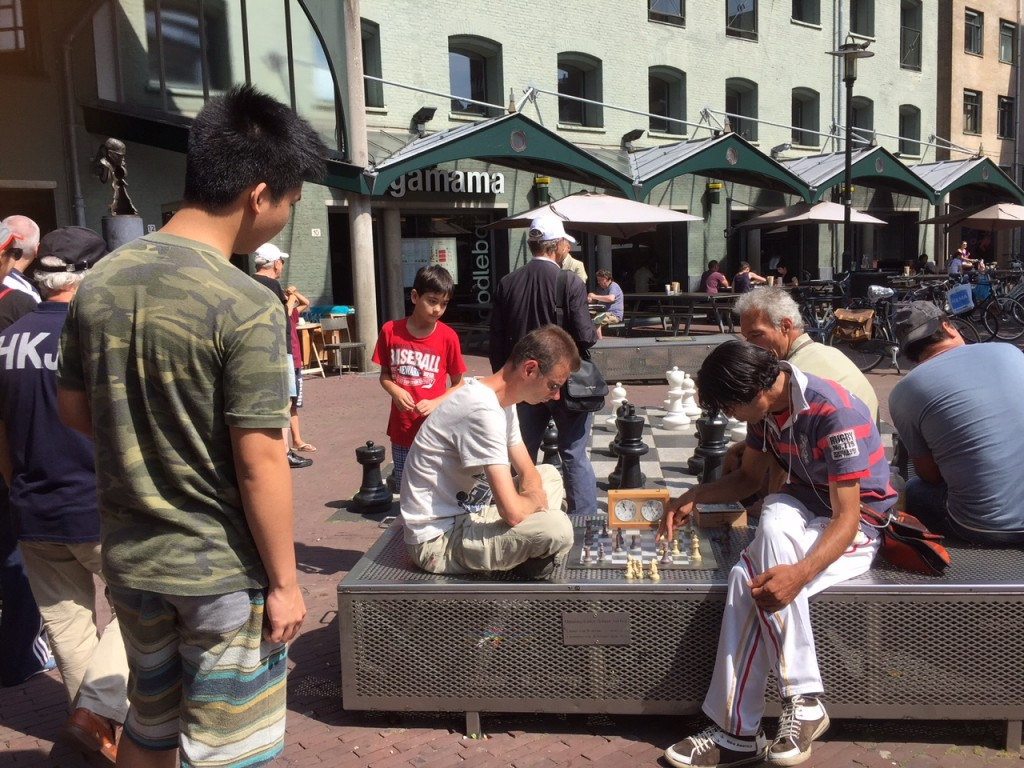 Melvin and Miguel ANgel study the chess game at Max Euwe Plein in Amsterdam